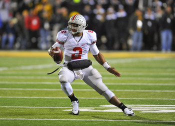IOWA CITY, IA - NOVEMBER 20:  Quarterback Terrelle Pryor #2 of the Ohio State Buckeyes scrambles for yards under pressure from University of Iowa Hawkeyes defenders during the second half of play at Kinnick Stadium on November 20, 2010 in Iowa City, Iowa.