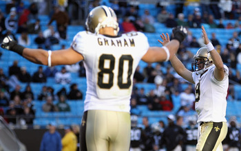 CHARLOTTE, NC - NOVEMBER 07:  Teammates Drew Brees #9 and Jimmy Graham #80 of the New Orleans Saints celebrate after a touchdown against the Carolina Panthers during their game at Bank of America Stadium on November 7, 2010 in Charlotte, North Carolina.