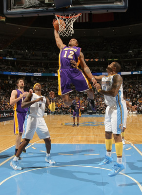 DENVER - NOVEMBER 11:  Shannon Brown #12 of the Los Angeles Lakers grabs a rebound and dunks the ball between Al Harrington #7 and Gary Forbes #0 of the Denver Nuggets at the Pepsi Center on November 11, 2010 in Denver, Colorado. The Nuggets defeated the