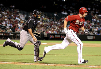 PHOENIX - SEPTEMBER 22:  Adam LaRoche #25 of the Arizona Diamondbacks runs to first base as catcher Miguel Olivo #21 of the Colorado Rockies chases him down for a strike out during the sixth inning of the Major League Baseball game at Chase Field on Septe