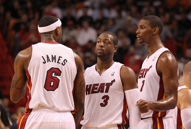 MIAMI, FL - NOVEMBER 29: LeBron James #6, Dwyane Wade #3, and Chris Bosh #1 of the Miami Heat talk during a game against the Washington Wizards at American Airlines Arena on November 29, 2010 in Miami, Florida. NOTE TO USER: User expressly acknowledges an
