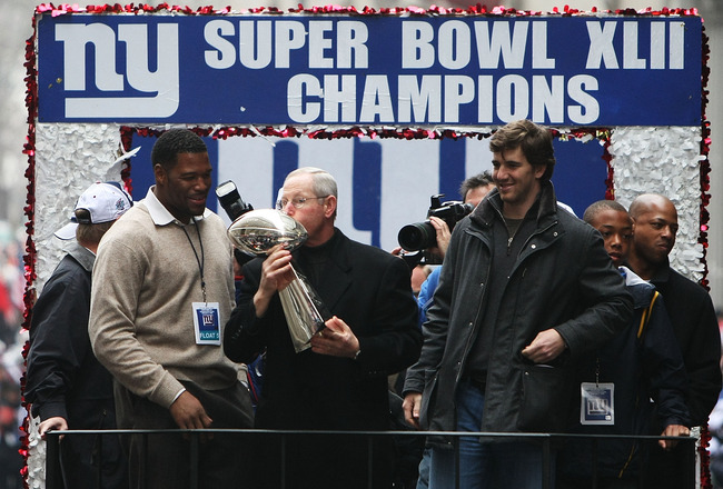 NEW YORK - FEBRUARY 05:  (L-R) Michael Strahan, Eli Manning and Head Coach Tom Coughlin of the New York Giants ride in a float along Broadway, also known as 'The Canyon of Heroes' during Super Bowl XLII victory parade in New York City.  (Photo by Al Bello