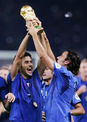 BERLIN - JULY 09:  Fabio Grosso (L) of Italy holds the World Cup trophy aloft following his team's victory in a penalty shootout at the end of the FIFA World Cup Germany 2006 Final match between Italy and France at the Olympic Stadium on July 9, 2006 in B