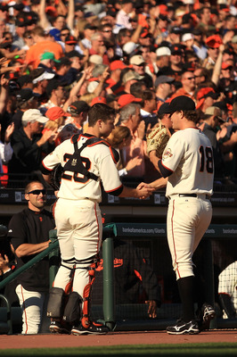 SAN FRANCISCO - OCTOBER 19:  Buster Posey #28 of the San Francisco Giants shakes hands with Matt Cain #18 in the middle of the seventh inning of Game Three of the NLCS against the Philadelphia Phillies during the 2010 MLB Playoffs at AT&T Park on October