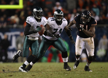 CHICAGO - NOVEMBER 28: Michael Vick #7 of the Philadelphia Eagles looks for a receiver as teammate Jason Peters #71 and Israel Idonije #71 of the Chicago Bears trail the play at Soldier Field on November 28, 2010 in Chicago, Illinois. The Bears defeated t