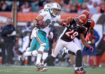 CINCINNATI - OCTOBER 31:  Brian Hartline #82 of the Miami Dolphins runs with the ball while defended by Leon Hall #29  of the Cincinnati Bengals during the NFL game at Paul Brown Stadium on October 31, 2010 in Cincinnati, Ohio.  (Photo by Andy Lyons/Getty