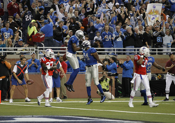 DETROIT - NOVEMBER 25:  Calvin Johnson #81 of the Detroit Lions celebrates a first quarter touchdown with teammate Brandon Pettigrew #84 to give the Lions a 7-3 lead over the New England Patriots at Ford Field on November 25, 2010 in Detroit, Michigan.  (