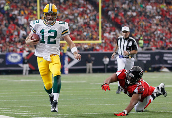 ATLANTA - NOVEMBER 28:  Quarterback Aaron Rodgers #12 of the Green Bay Packers rushes upfield away from Corey Peters #91 of the Atlanta Falcons at Georgia Dome on November 28, 2010 in Atlanta, Georgia.  (Photo by Kevin C. Cox/Getty Images)