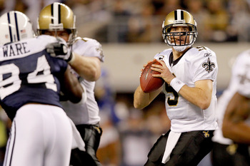ARLINGTON, TX - NOVEMBER 25:  Quarterback Drew Brees #9 of the New Orleans Saints looks for an open receiver while playing the Dallas Cowboys at Cowboys Stadium on November 25, 2010 in Arlington, Texas.  (Photo by Matthew Stockman/Getty Images)