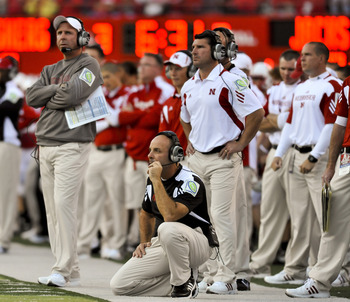LINCOLN, NEBRASKA - SEPTEMBER 25: Nebraska co-defensive coordinator Carl Pelini (kneeling) and head coach Bo Pelini (L) watch their defense against the South Dakota State Jackrabbits during first half action of their game at Memorial Stadium on September