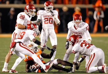 STILLWATER, OK - NOVEMBER 27:  Receiver Hubert Anyiam #84 of the Oklahoma State Cowboys is surrounded by the Oklahoma Sooners defense at Boone Pickens Stadium on November 27, 2010 in Stillwater, Oklahoma.  The Sooners beat the Cowboys 47-41.  (Photo by To