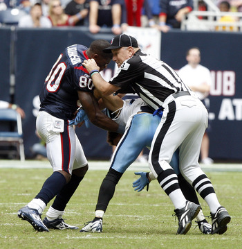 HOUSTON - NOVEMBER 28:  Wide receiver Andre Johnson #80 of the Houston Texans is separated by umpire Garth DeFerlice #53 from cornerback Cortland Finnegan #31 of the Tennessee Titans after the two exchanged punches in the fourth quarter at Reliant Stadium