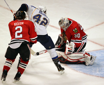 CHICAGO - NOVEMBER 30: Corey Crawford #50 of the Chicago Blackhawks stops a shot with his stick by David Backes #42 of the St. Louis Blues as teammate Duncan Keith #2 closes in at the United Center on November 30, 2010 in Chicago, Illinois. The Blackhawks