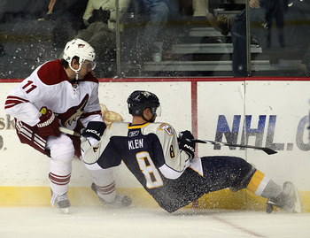 NASHVILLE, TN - NOVEMBER 30: Martin Hanzal #11 of the Phoenix Coyotes trips up Kevin Klein #8 of the Nashville Predators at the Bridgestone Arena on November 30, 2010 in Nashville, Tennessee. The Predators defeated the Coyotes 3-0. (Photo by Bruce Bennett