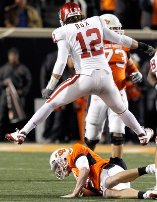 STILLWATER, OK - NOVEMBER 27:  Linebacker Austin Box #12 of the Oklahoma Sooners leaps over quarterback Brandon Weeden #3 of the Oklahoma State Cowboys after Weeden was sacked for a loss at Boone Pickens Stadium on November 27, 2010 in Stillwater, Oklahom