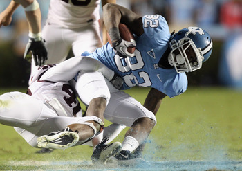 CHAPEL HILL, NC - NOVEMBER 13:  The defense of the Virginia Tech Hokies takes down Todd Harrelson #82 of the North Carolina Tar Heels hard to the ground during their game at Kenan Stadium on November 13, 2010 in Chapel Hill, North Carolina.  (Photo by Str