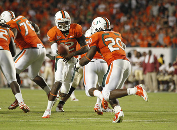 MIAMI, FL - OCTOBER 9: Jacory Harris #12 hands the ball off to Damien Berry #20 of the Miami Hurricanes against the Florida State Seminoles on October 9, 2010 at Sun Life Stadium in Miami, Florida. The Seminoles defeated the Hurricanes 45-17. (Photo by Jo