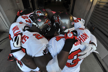 BALTIMORE, MD - NOVEMBER 28:  Carnell Williams #24 and Earnest Graham #34 of the Tampa Bay Buccaneers huddle with teammates before the game against the Baltimore Ravens at M&T Bank Stadium on November 28, 2010 in Baltimore, Maryland. The Ravens defeated t