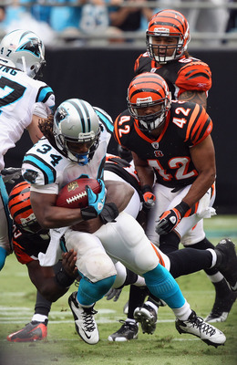 CHARLOTTE, NC - SEPTEMBER 26:  DeAngelo Williams #34 of the Carolina Panthers is tackled by the defense of the Cincinnati Bengals during their game at Bank of America Stadium on September 26, 2010 in Charlotte, North Carolina.  (Photo by Streeter Lecka/Ge