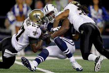 ARLINGTON, TX - NOVEMBER 25:  Tracy Porter #22 and Jonathan Vilma #51 of the New Orleans Saints tackle Jason Whitten #82 of the Dallas Cowboys at Cowboys Stadium on November 25, 2010 in Arlington, Texas.  (Photo by Matthew Stockman/Getty Images)