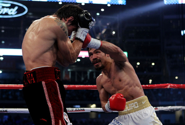 ARLINGTON, TX - NOVEMBER 13:  Manny Pacquiao (R in white trunks) of the Philippines lands a punch against Antonio Margarito (black trunks) of Mexico during their WBC World Super Welterweight Title bout at Cowboys Stadium on November 13, 2010 in Arlington,