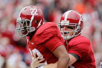 TUSCALOOSA, AL - NOVEMBER 26:  Quarterback Greg McElroy #12 and Mark Ingram #22 of the Alabama Crimson Tide react after Ingram's touchdown against the Auburn Tigers at Bryant-Denny Stadium on November 26, 2010 in Tuscaloosa, Alabama.  (Photo by Kevin C. C