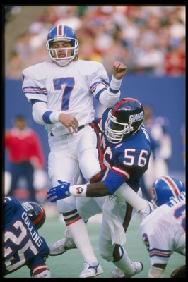 1986:  Quarterback John Elway of the Denver Broncos is sacked by linebacker Lawrence Taylor of the New York Giants during a game at Giants Stadium in East Rutherford, New Jersey.  The Giants won the game 19-16. Mandatory Credit: T. G. Higgins  /Allsport