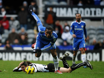 NEWCASTLE UPON TYNE, ENGLAND - NOVEMBER 28:  Didier Drogba of Chelsea hurdles Andy Carroll of Newcastle United during the Barclays Premier League match between Newcastle United and Chelsea at St James' Park on November 28, 2010 in Newcastle, England.  (Ph