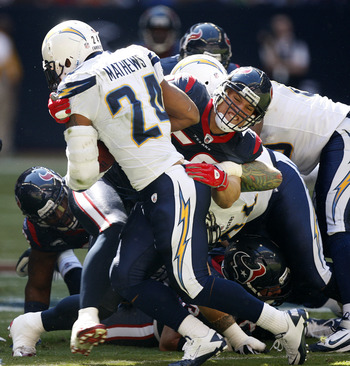 HOUSTON - NOVEMBER 07:  Running back  Ryan Mathews #24 of the San Diego Chargers is tackled by linebacker Brian Cushing #56 of the Houston Texans at Reliant Stadium on November 7, 2010 in Houston, Texas.  (Photo by Bob Levey/Getty Images)