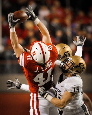 LINCOLN, NE - NOVEMBER 26: Jake Long #41 of the Nebraska Cornhuskers catches a pass over Travis Sandersfeld #19 and Jalil Brown #23 of the Colorado Buffaloes during the second half of their game at Memorial Stadium on November 26, 2010 in Lincoln, Nebrask