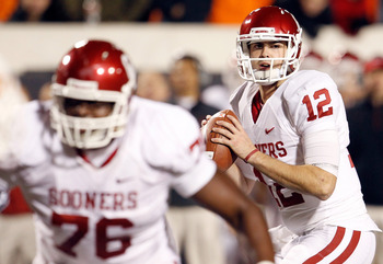 STILLWATER, OK - NOVEMBER 27:  Quarterback Landry Jones #12 of the Oklahoma Sooners looks for an open receiver against the Oklahoma State Cowboys at Boone Pickens Stadium on November 27, 2010 in Stillwater, Oklahoma.  The Sooners beat the Cowboys 47-41. (