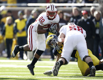 ANN ARBOR, MI - NOVEMBER 20: James White #20 of the Wisconsin Badgers jumps arond the block of teammate Ricky Wagner #58 while playing the Michigan Wolverines at Michigan Stadium on November 20, 2010 in Ann Arbor, Michigan.  (Photo by Gregory Shamus/Getty