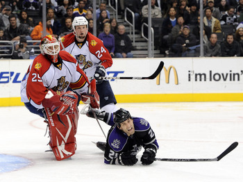 LOS ANGELES, CA - DECEMBER 02:  Jarret Stoll #28 of the Los Angeles Kings is upended by Tomas Vokoun #29 of the Florida Panthers as Bryan McCabe #24 looks on during the second period on December 2, 2010 in Los Angeles, California.  (Photo by Harry How/Get