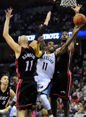 MEMPHIS, TN - NOVEMBER 20:  Mike Conley #11 of the Memphis Grizzlies drives between Zydrunas Ilgauskas #11 and LeBron James #6 of the Miami Heat at FedExForum on November 20, 2010 in Memphis, Tennessee. The Grizzlies won 97-95.  NOTE TO USER: User express