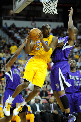 LAS VEGAS - OCTOBER 13:  Kobe Bryant #24 of the Los Angeles Lakers drives between Antoine Wright #3 (L) and Carl Landry #24 of the Sacramento Kings during their preseason game at the Thomas & Mack Center October 13, 2010 in Las Vegas, Nevada. The Lakers w