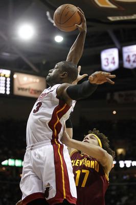 CLEVELAND, OH - 02 de dezembro: Dwyane Wade # 3 do Miami Heat recebe a cesta para uma enterrada passado Anderson Varejão # 17 do Cleveland Cavaliers na Quicken Loans Arena em 02 de dezembro de 2010 em Cleveland, Ohio. NOTA AO USUÁRIO: Usuário expressamente reconhece e um