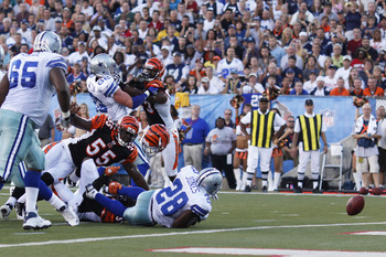 CANTON, OH - AUGUST 8: Felix Jones #28 of the Dallas Cowboys fumbles the football near the goal line after being his by Roy Williams #31 of the Cincinnati Bengals during the 2010 Pro Football Hall of Fame Game at the Pro Football Hall of Fame Field at Faw