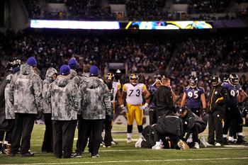 BALTIMORE, MD - DECEMBER 05:  The Baltimore Ravens and the Pittsburgh Steelers look on while tight end Heath Miller #83 of the Pittsburgh Steelers is tended to on the field after being injured during the third quarter of the game at M&amp;T Bank Stadium on De
