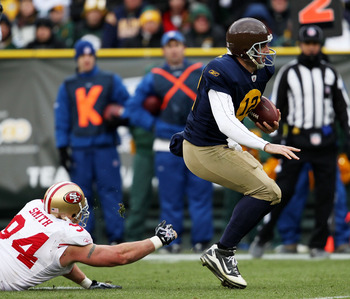 GREEN BAY, WI - DECEMBER 05: Aaron Rodgers #12 of the Green Bay Packers breaks away from Justin Smith #94 of the San Francisco 49ers on a run for a first down at Lambeau Field on December 5, 2010 in Green Bay, Wisconsin. The Packers defeated the 49ers 34-