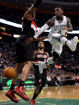 BOSTON - DECEMBER 01:  Nate Robinson #4 of the Boston Celtics passes the ball as LaMarcus Aldridge #12 of the Portland Trailblazers defends on December 1, 2010 at the TD Garden in Boston, Massachusetts.  NOTE TO USER: User expressly acknowledges and agree