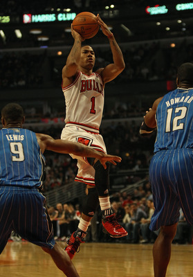CHICAGO, IL - DECEMBER 01: Derrick Rose #1 of the Chicago Bulls shoots against Rashard Lewis #9 and Dwight Howard #12 of the Orlando Magic at the United Center on December 1, 2010 in Chicago, Illinois. The Magic defeated the Bulls 107-78. NOTE TO USER: Us