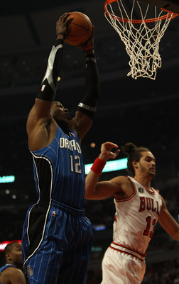CHICAGO, IL - DECEMBER 01: Dwight Howard #12 of the Orlando Magic grabs a rebound near Joakim Noah #13 of the Chicago Bulls at the United Center on December 1, 2010 in Chicago, Illinois. NOTE TO USER: User expressly acknowledges and agrees that, by downlo
