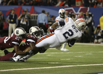 ATLANTA - DECEMBER 4:  Quarterback Cam Newton #2 of the Auburn Tigers dives in for a first quarter touchdown while safety DeVonte Holloman #21 and linebacker Tony Straughter #44 of the South Carolina Gamecocks try to stop him during the 2010 SEC Champions