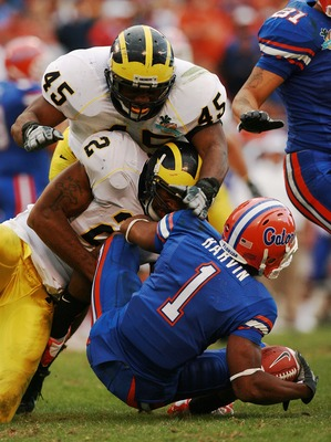 ORLANDO, FL - JANUARY 01:  Wide receiver Percy Harvin #1 of the Florida Gators is brought down by linebackers Shawn Crable #2 and Obi Ezeh #45 of the Michigan Wolverines in the Capital One Bowl at Florida Citrus Bowl on January 1, 2008 in Orlando, Florida