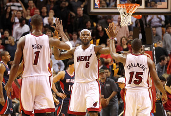 MIAMI, FL - DECEMBER 04:  LeBron James #6 of the Miami Heat is congratulated by Chris Bosh #1 and Mario Chalmers #15 during a game against the Atlanta Hawks at American Airlines Arena on December 4, 2010 in Miami, Florida. NOTE TO USER: User expressly ack