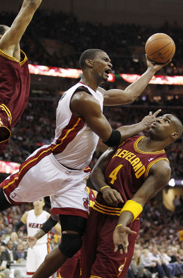 CLEVELAND, OH - DECEMBER 02:  Chris Bosh #1 of the Miami Heat gets a shot off over Antawn Jamison #4 of the Cleveland Cavaliers at Quicken Loans Arena on December 2, 2010 in Cleveland, Ohio. NOTE TO USER: User expressly acknowledges and agrees that, by do