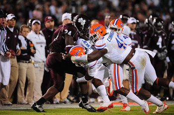 STARKVILLE, MS - OCTOBER 24:  Running back Anthony Dixon # 24 of the Mississippi State Bulldogs is tackled by Jermaine Cunningham # 49 and Janoris Jenkins # 1 of the Florida Gators, at Davis Wade Stadium on  October 24, 2009 in Starkville, Mississippi  (P