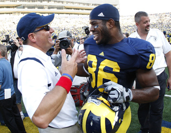 ANN ARBOR, MI - SEPTEMBER 05:  Head coach Rich Rodriguez of the Michigan Wolverines talks with Kevin Koger #86 after beating the Western Michigan Broncos 31-7 on September 5, 2009 at Michigan Stadium in Ann Arbor, Michigan.  (Photo by Gregory Shamus/Getty