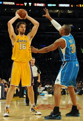 Pau Gasol of the Lakers plays keep away from New Orleans Hornets forward David West