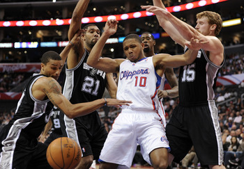 LOS ANGELES, CA - DECEMBER 01:  Eric Gordon #10 of the Los Angeles Clippers has the ball knocked away by Tim Duncan #21, Matt Bonner #15 and George Hill #3 of the San Antonio Spurs Los Angeles at the Staples Center on December 1, 2010 in Los Angeles, Cali